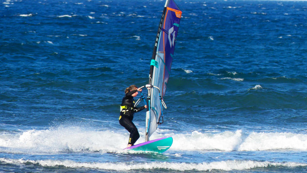 a windsurfer starting a jibe close to the beach