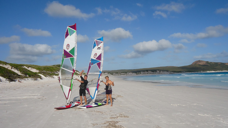 Two windsurfers standing on the beach with the sails in their hands