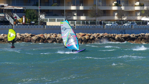Wingfoil and Windsurfer on the water surfing