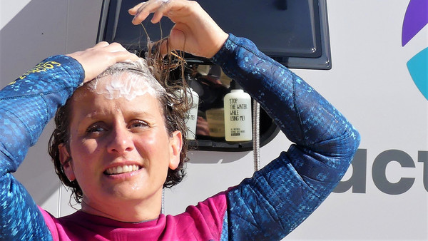 A woman taking her shower in front of a campervan