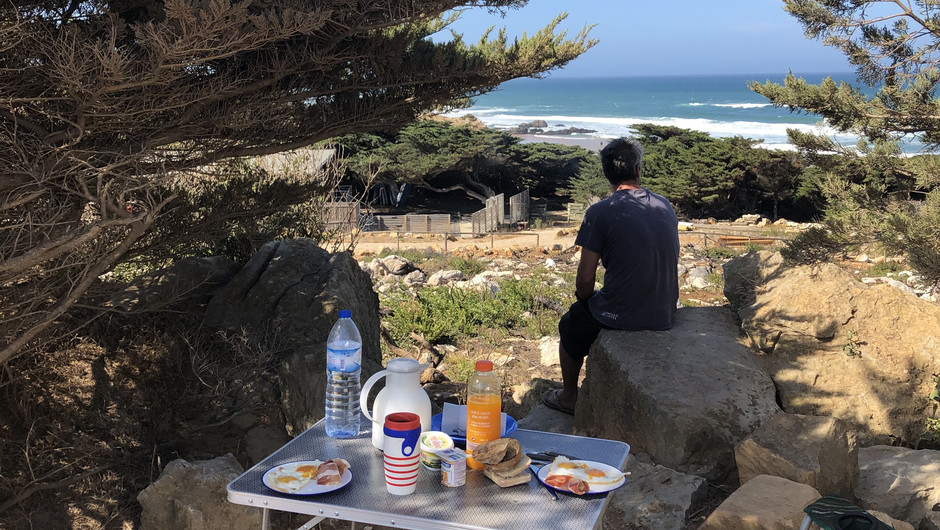 breakfast camping table dressed with view to the ocean