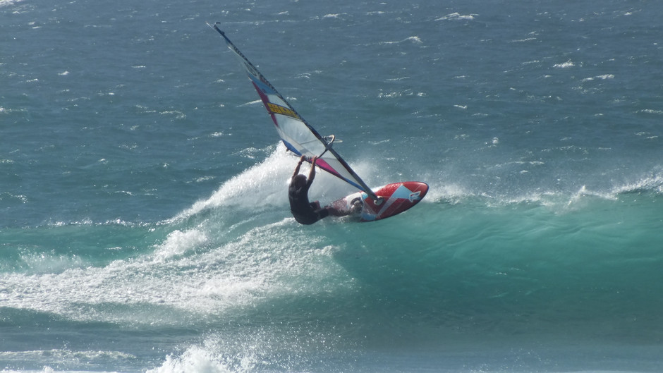 a windsurfer riding on the top of the wave
