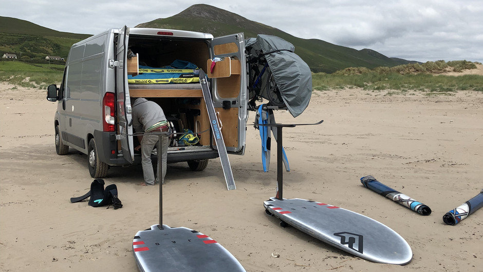 Two windsurf foil boards laying on the beach in front if a van with open rear doors