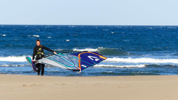 a windsurfer women carrying equipment out of the water and walking on the sand